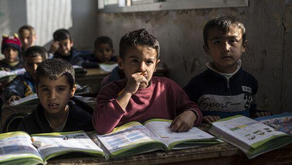 На уроке в школе поселения для беженцев в населенном пункте Аль-Ком провинции Кунейтра. Сирия, 15.12.2015