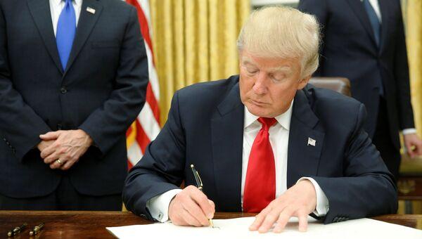 Трамп подписывает указ. Архивное фото