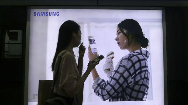 Девушка на фоне рекламы смартфона