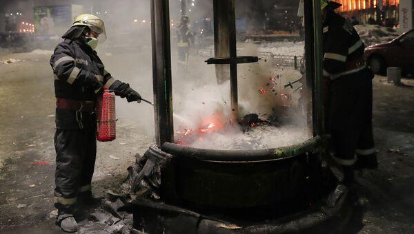 Пожарные тушат горящий киоск после акции протеста в Румынии, 2 февраяля 2017