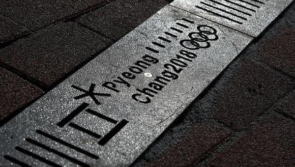 Символика XXIII Олимпийских игр на решетки водостока в олимпийском парке в Пхенчхане