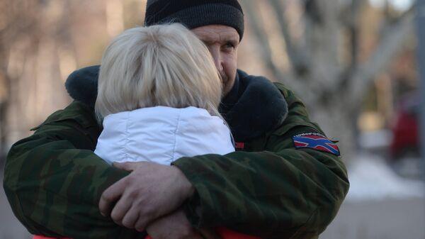 Женщина прощается с ополченцем ДНР перед отправкой автобусов с беженцами из Донецка в Россию