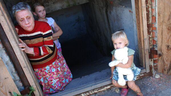 Дети и женщина, живущие в бомбоубежище в одном из окраинных районов Донецка, продолжающих подвергаться обстрелам со стороны украинских силовиков