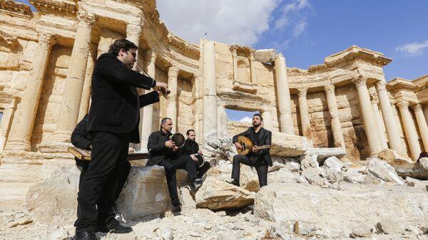Сирийские музыканты играют на месте разрушенного римского амфитеатра в древнем городе Пальмира, Сирия