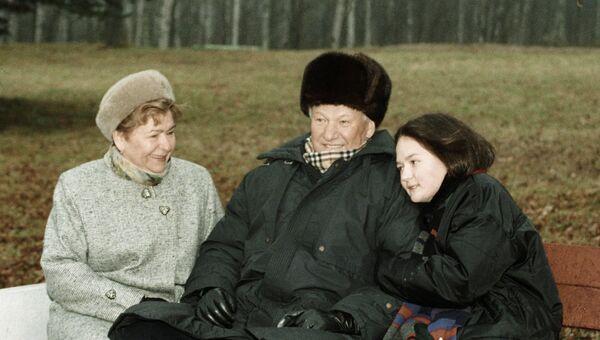 Президент РФ Борис Ельцин сидит на скамье во время прогулки с супругой Наиной и внучкой Машей