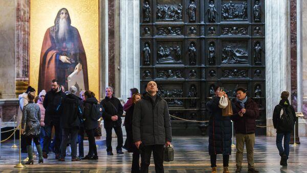 Туристы на экскурсии в Исаакиевском соборе. На втором плане - икона с изображением святого Исаакия