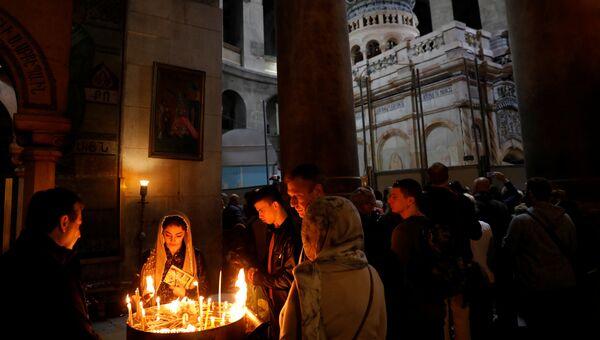 Прихожане зажигают свечи в отреставрированной Кувуклии в храме Гроба Господня в Иерусалиме