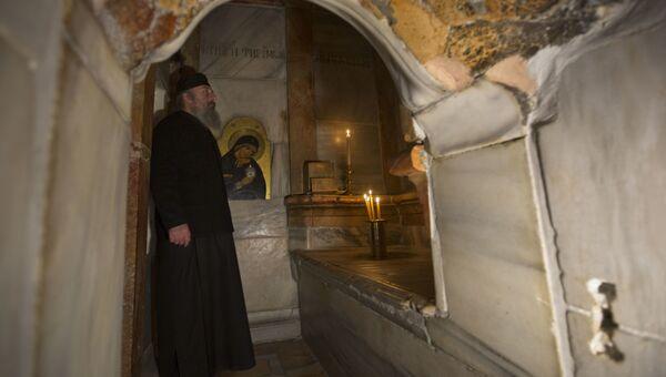 Греческий священник внутри отреставрированной Кувуклии в храме Гроба Господня в Иерусалиме