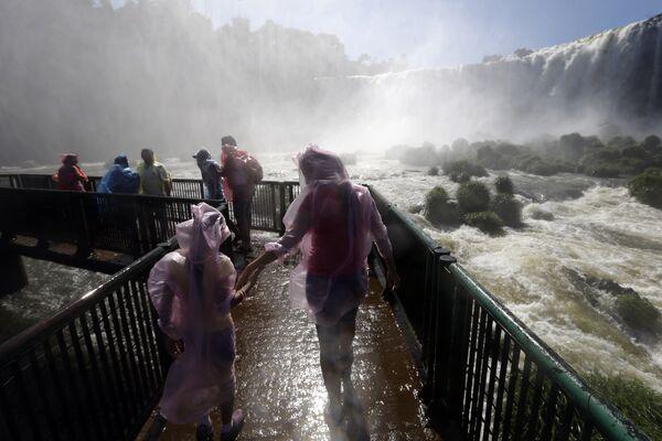 Туристы посещают водопад Игуасу в Бразилии