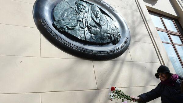 Жительница возлагает цветы на церемонии открытия мемориальной доски оперной певице Галине Вишневской и музыканту Мстиславу Ростроповичу на доме 13 в Газетном переулке в Москве