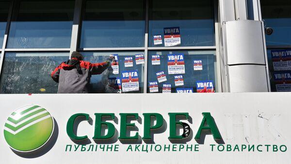 Рабочий очищает фасад центрального отделения дочернего предприятия Сбербанка России в Киеве от листовок. Архивное фото