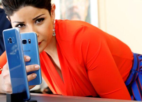 Девушка фотографирует смартфон Samsung Galaxy S8 + с Galaxy S7 на презентации в Нью-Йорке