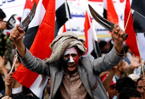 Мужчина размахивает кинжалами во время празднования годовщины военного вмешательства коалиции под руководством Саудовской Аравии в Сане, Йемен
