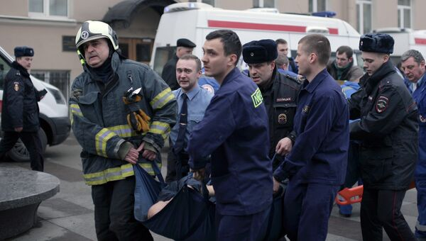Сотрудники спецслужб несут пострадавшего у станции метро Технологический институт в Санкт-Петербурге