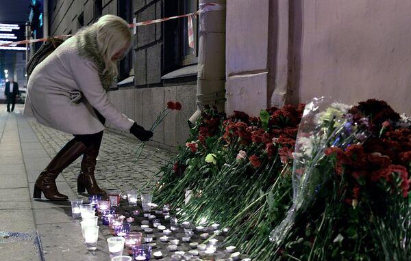 Женщина возлагает цветы рядом со станцией метро Технологический институт в память о погибших в результате взрыва в метро Санкт-Петербурга