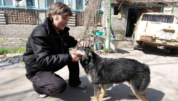 Местный житель с собакой на улице Привокзальной в прифронтовом поселке Донецк-Северный в Донецкой области
