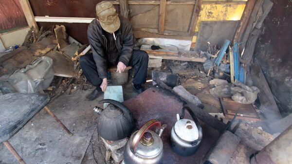 Местный житель следит на улице за печкой, на который жители многоквартирного дома греют чайники