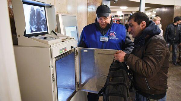 Сотрудник службы безопасности метрополитена досматривает пассажира в вестибюле станции метро в Москве. Архивное фото