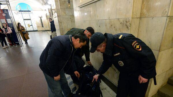 Сотрудник полиции проверяет вещи у пассажиров на станции Московского метрополитена