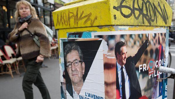 Плакаты с изображениями кандидатов в президенты Франции Жан-Люка Меланшона и Франсуа Фийона в Париже
