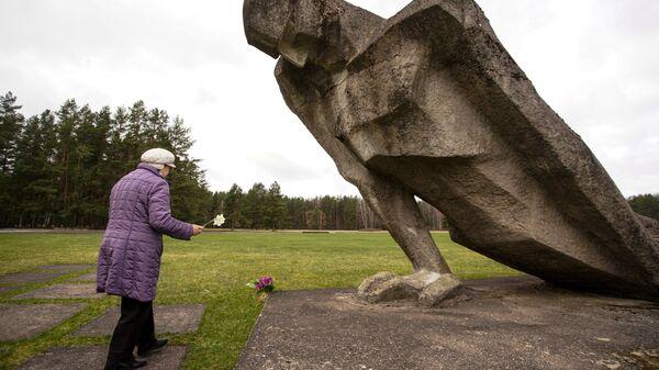 Женщина возлагает цветы к мемориалу памяти жертв фашизма на месте концлагеря Саласпилс в Латвии