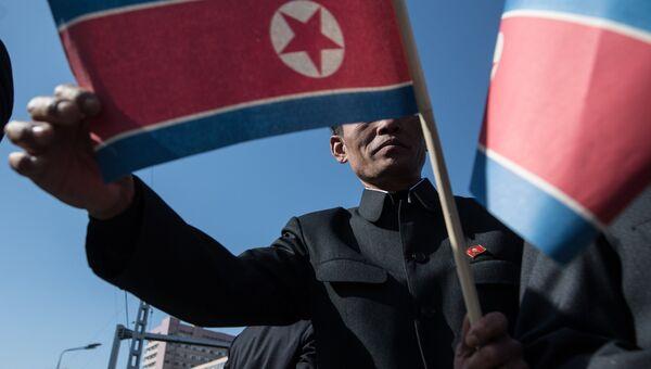 Житель Пхеньяна с флагом КНДР. Архивное фото