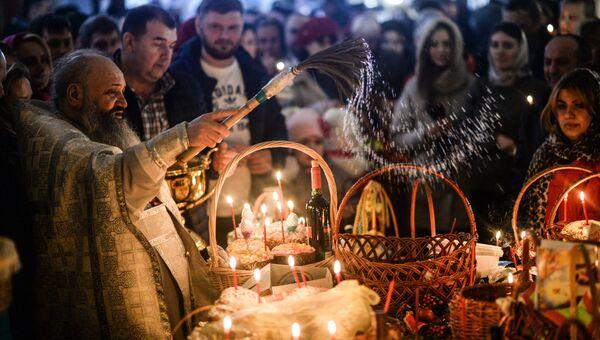 Верующие во время освящения куличей и пасхальных яиц в Великую субботу в Варлаамо-Хутынском Спасо-Преображенском женском монастыре в Великом Новгороде