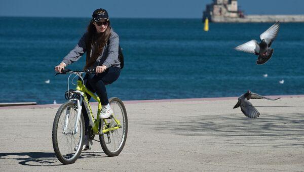 Девушка на велосипеде на набережной Феодосии