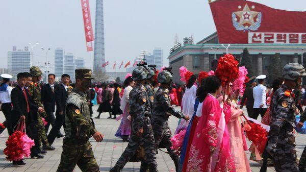 Люди после окончания парада, приуроченного к 105-й годовщине со дня рождения основателя северокорейского государства Ким Ир Сена, в Пхеньяне