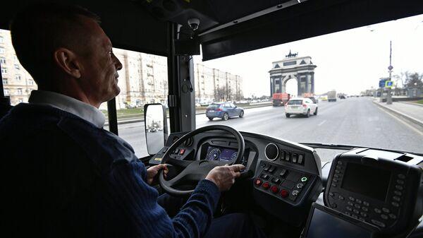 Водитель в новом электробусе с возможностью зарядки на маршруте во время презентации в Москве