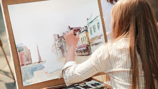 Девушка рисует левой рукой. Архивное фото