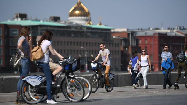 Москвичи на велосипедах из городского общественного проката на набережной Парка искусств Музеон