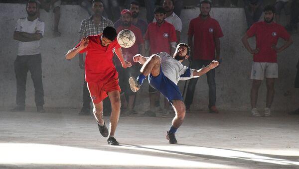 Игроки во время футбольного матча между командами сотрудников общества Красного Креста и Красного Полумесяца и студентами в сирийском городе Дейр-эз-Зор