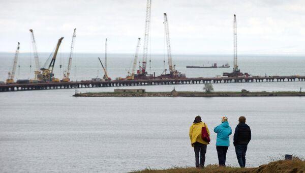 Люди наблюдают за строительством моста через Керченский пролив в Крыму. Архивное фото