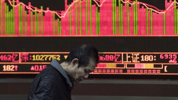 Прохожий на фоне табло с биржевыми котироваками в Шанхае, КНР