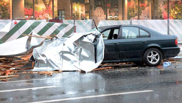 Сорванный ураганом рекламный щит на припаркованном автомобиле в Москве. 29 мая 2017