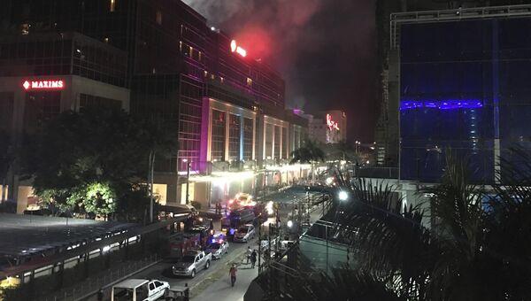 Дым над зданием отеля и казино Resorts World в центре Манилы, Филиппины