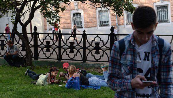 Молодые люди с мобильными телефонами. Архивное фото
