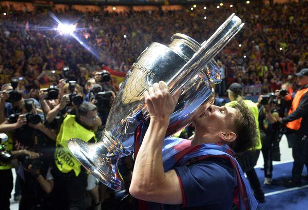 Нападающий футбольного клуба Барселона Лионель Месси целует кубок Лиги чемпионов. 6 июня 2015