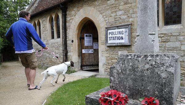 Мужчина с собакой возле участка для голосования на досрочных парламетских выборах в Великобритании. 8 июня 2017