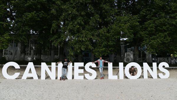 Посетители фестиваля-показа Каннские львы в Москве фотографируются на фоне инсталляции Cannes Lions