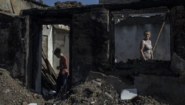 Жители в пострадавшем во время обстрела поселке Старомихайловка Донецкой области. Архивное фото