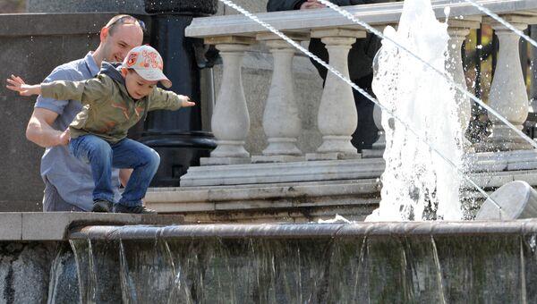 Мужчина с ребенком у одного из фонтанов на Манежной площади в Москве. Архивное фото