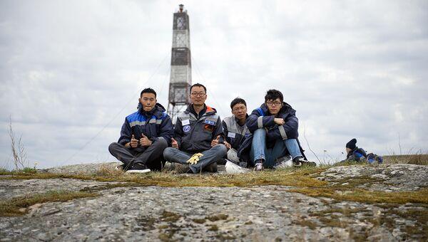 Команда китайских участников на фоне маяке, остров Соммерс