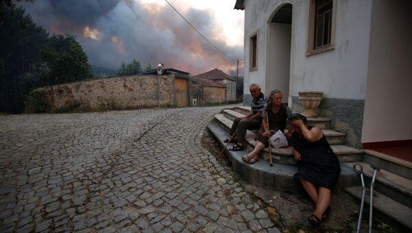 Местные жители сидят возле дома во время лесных пожаров в Португалии
