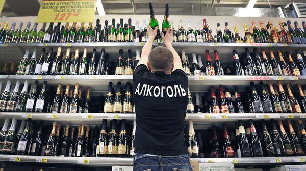 Продавец расставляет на полках бутылки шампанского вина