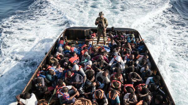 Сотрудник Ливийской береговой охраны во время спасения нелегальных мигрантов, пытающихся добраться до Европы, недалеко от Эз-Завия