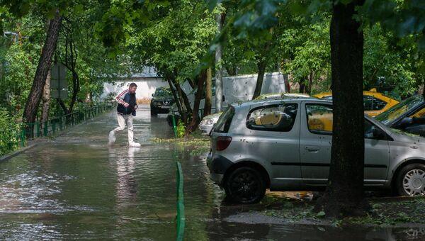 Потоки воды в одном из дворов после дождя в Москве