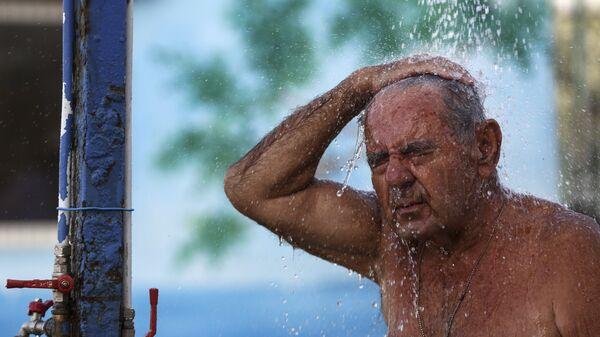 Мужчина во время жары в пригороде Афин, Греция. 1 июля 2017