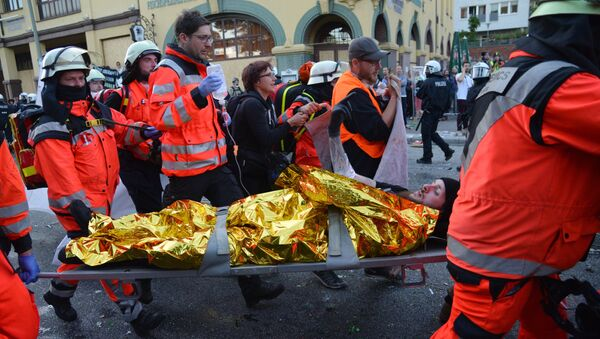 Спасатели помогают участнику акции протеста в преддверии саммита G20 в Гамбурге